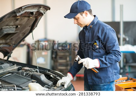 Portrait of a mechanic holding a wrench in his garage