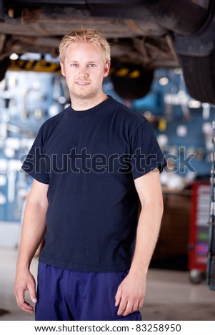 Portrait of a mechanic looking at the camera in auto repair shop - stock photo