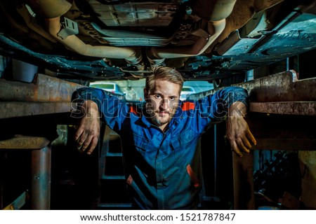 Portrait of a mechanic standing in a protective blue suit in a garage under a car. Car service concept. Car repair and maintenance. Mechanic examining under the car at the repair garage.