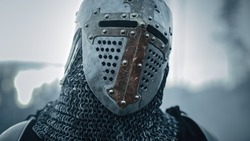Portrait of a Medieval Knight on Battlefield, Closed Helmet Ready for Battle. Portrait of Mighty Warrior, King, Soldier at War, Conquest, Crusade. Dramatic Scene, Cinematic Historic Reenactment