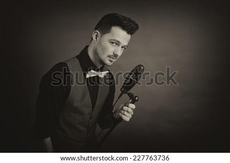 Portrait of a men holding a microphone looking weird at the camera