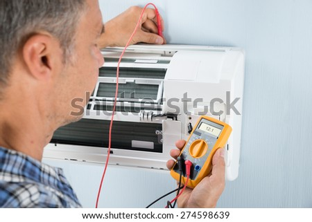 Portrait Of A Mid-adult Male Technician Testing Air Conditioner With Digital Multimeter
