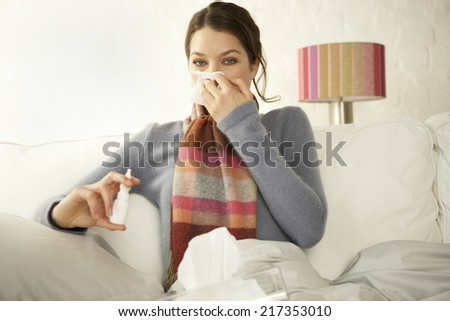 Portrait of a mid adult woman holding a bottle of nasal spray and suffering from cold