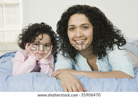 Portrait of a mid adult woman with her daughter lying on the bed