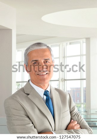 Portrait of a middle aged businessman wearing a light tan suit with his arms folded in a modern office setting. Vertical format, with the man smiling.