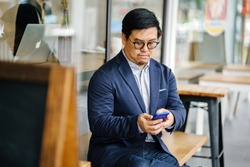Portrait of a middle-aged Chinese Asian man in a casual suit and glasses sitting on a bench at a cafe and using his smartphone.