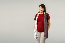 Portrait of a middle aged Chinese Asian woman in a studio against a white backdrop. She is wearing a red dress, khakis and a colorful scarf. The woman is smiling.