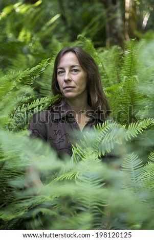 Portrait of a middle aged female hiker surrounded by ferns.