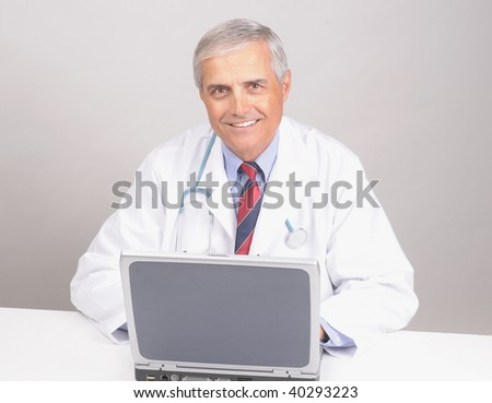 Portrait of a Middle Aged  Male Doctor in Lab Coat with Stethoscope and Laptop Computer over gray background