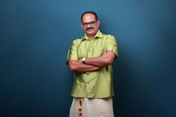 Portrait of a middle aged man wearing Kerala style traditional dress with folded hands