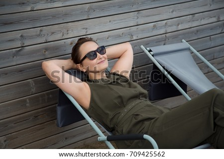 Portrait of a middle aged older woman relaxing on lounge patio beach chair outdoors on holidays/vacation. Nice picture of relaxed smiling woman wearing sunglasses and jumpsuit.