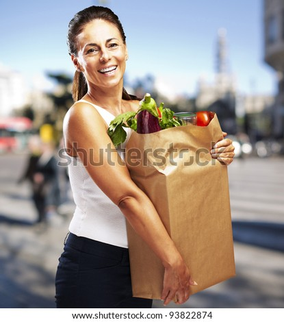 portrait of a middle aged woman carrying a purchase at a crowded street