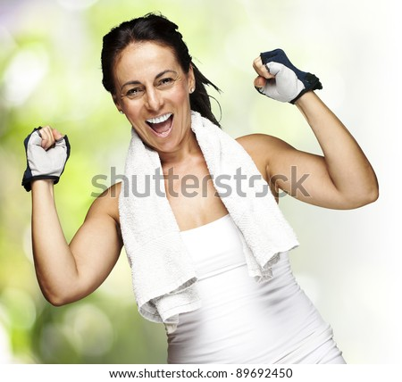 portrait of a middle aged woman gesturing win symbol against a nature background