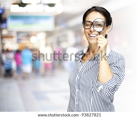 portrait of a middle aged woman looking through a magnifying glass against a crowded place