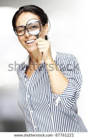 portrait of a middle aged woman looking through a magnifying glass indoor