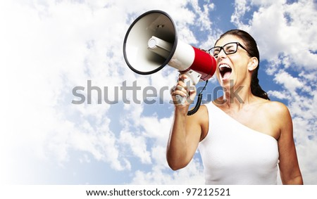 portrait of a middle aged woman shouting with a megaphone against a cloudy sky