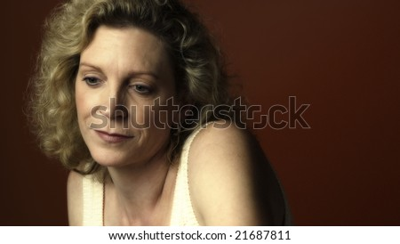 Portrait of a middle aged woman sitting in a chair and looking sad