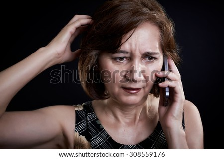 Portrait of a middle aged woman talking on the phone. Worrisome phrase. Hand on head.