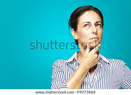 portrait of a middle aged woman thinking against a blue background