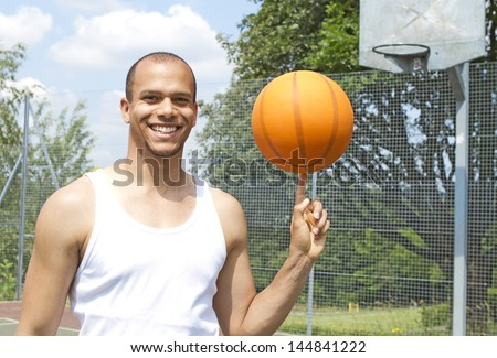Portrait of a MIxed race basketball Player Spinning the Ball on an outdoor basketball court