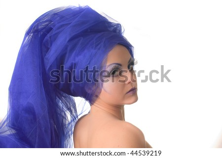 Portrait of a model with an unusual theatrical makeup in a blue headdress
