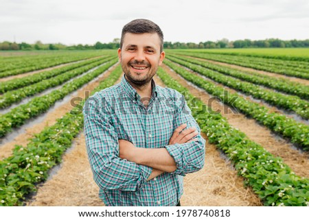portrait of a modern bearded farmer man with crossed arms looking at camera stands in the agricultural field, Cheerful male worker in agricultural farm. Agriculture farming.