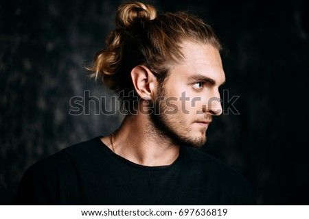 Portrait of a modern young man with long hair. Studio portrait over grunge background. Urban style.