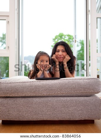 Portrait of a mother and daughter in home interior looking at the camera with their heads leaning on hands