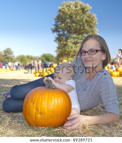 Portrait of a mother and her baby girl with bright orange pumpkin