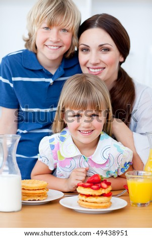 Portrait of a mother and her children having breakfast in the kitchen