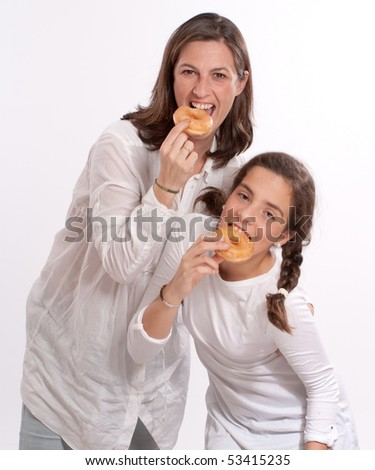 Portrait of a mother and her daughter happily eating doughnuts