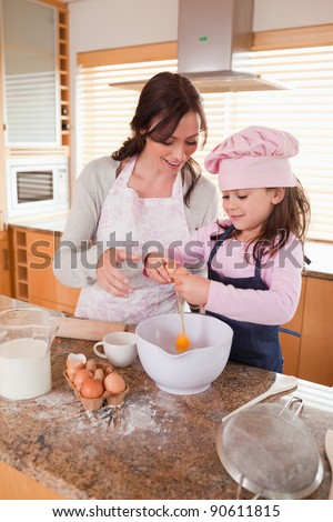 Portrait of a mother and her happy daughter baking in a kitchen