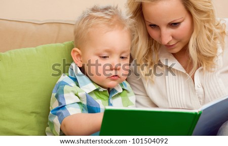 Portrait of a mother and son reading a book together at home.
