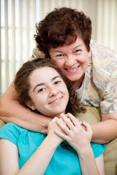 Portrait of a mother giving her teen daughter a big hug.