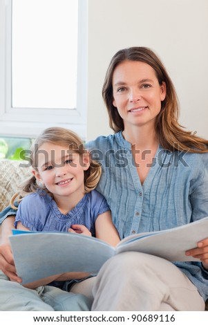 Portrait of a mother reading a book to her daughter in a living room