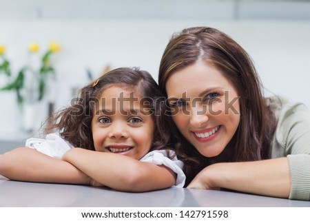 Portrait of a mother with her daughter leaning on the counter