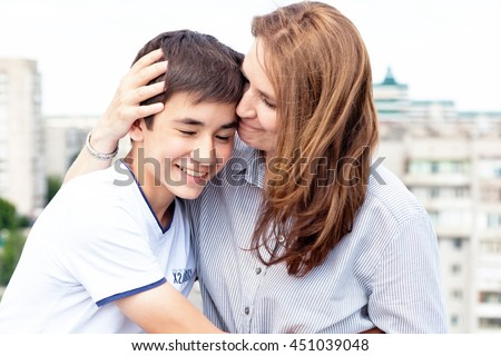 Portrait of a mother with her son teenager. Tenderness, love, multinational family