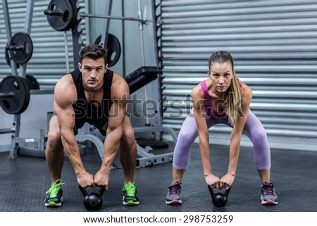 Portrait of a muscular couple lifting kettlebells at the health club