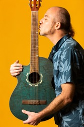 Portrait of a Musician kissing his blue acoustic guitar against a yellow background