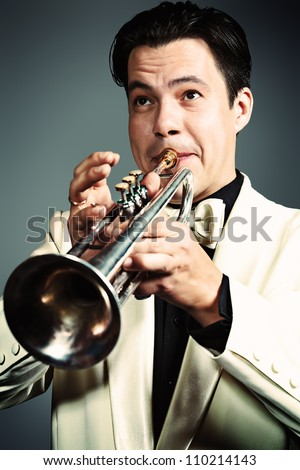 Portrait of a musician playing the trumpet at studio.