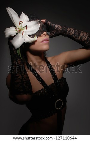 Portrait of a mysterious woman with a flower in her hair