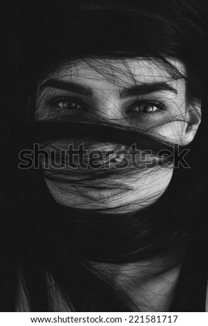 Portrait of a mysterious woman with her long brown hair wrapped in strands across her face looking at the camera with seductive luminous eyes, monochrome head and shoulders image