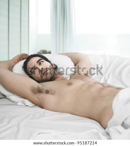 Portrait of a naked man in bed with window behind him