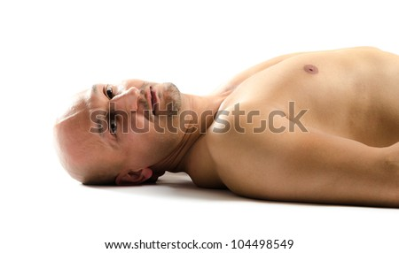 Portrait of a naked man lying on the floor looking up - stock photo