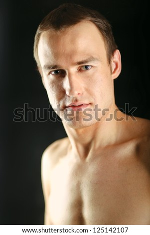 Portrait of a naked muscular man, isolated on black background