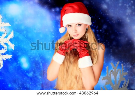 Portrait of a naked young woman wearing christmas cap and red gloves over sky of stars and snow.