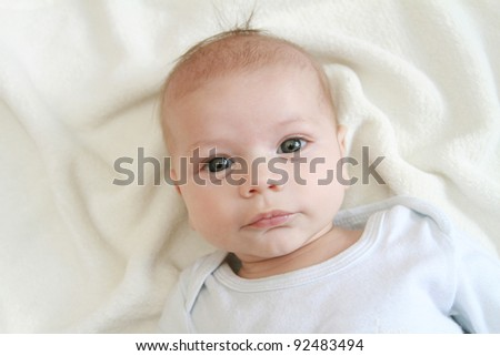 Portrait of a newborn baby's face on blanket - stock photo