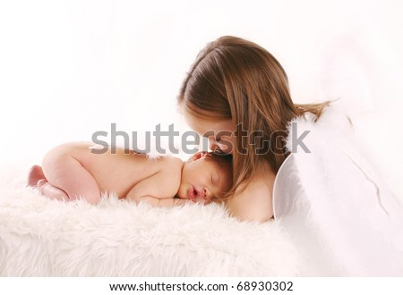 Portrait of a newborn baby with angel wings being kissed by big sister wearing white fairy wings