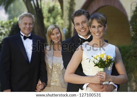 Portrait of a newly married couple embracing with parents standing in the background