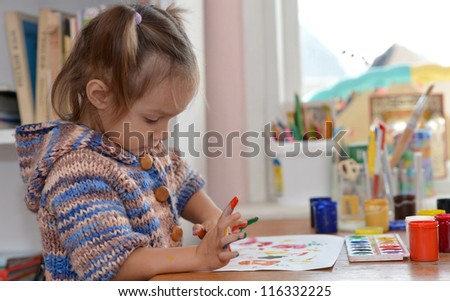 Portrait of a nice baby draws paints at the table